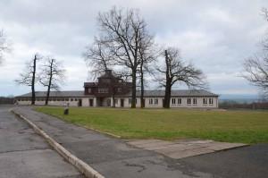 Bâtiment de l'entrée principale et sa porte en fer forgé (1938) portant l'exergue « Jedem das Seine » (à chacun son dû). Le commandant a voulu qu'elle soit lisible depuis l'intérieur. Les prisonniers rassemblés sur la place d'appel devaient ainsi l'avoir devant les yeux. Le site du mémorial de Buchenwald (http://www.buchenwald.de) explique que cette inscription remonte à la maxime juridique, datant de deux mille ans « suum cuique »: « Iuris praecepta sunt haec: honeste vivere, alterum non laedere, suum cuique tribuere. » - « Les principes fondamentaux du droit sont les suivants: vivre honnêtement, ne faire de tort à personne, donner à chacun son dû. »
